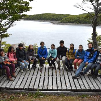 Grupo de niños y tutor sentados y descansando en un mirador