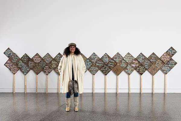 La artista neozelandesa de origen maorí, Charlotte Graham junto a su trabajo Picket waka